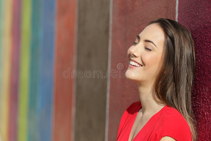 Happy woman leaning on a colorful wall in the street royalty free stock images