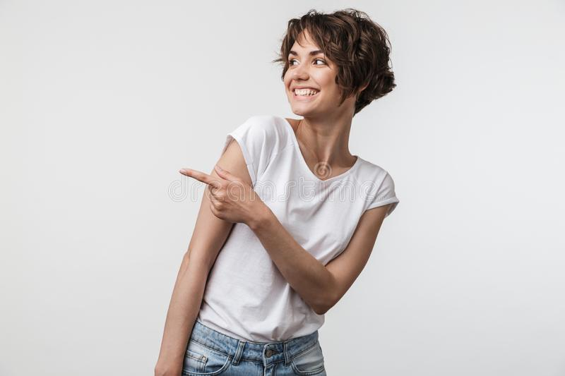 Portrait of happy woman with short hair in basic t-shirt rejoicing and pointing finger at copyspace royalty free stock images