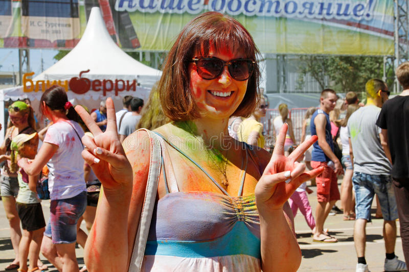 Portrait of happy woman showing victory sign on Holi color festival in Volgograd stock photos