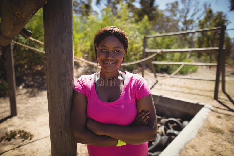 Portrait of happy woman standing with arms crossed during obstacle course royalty free stock photo