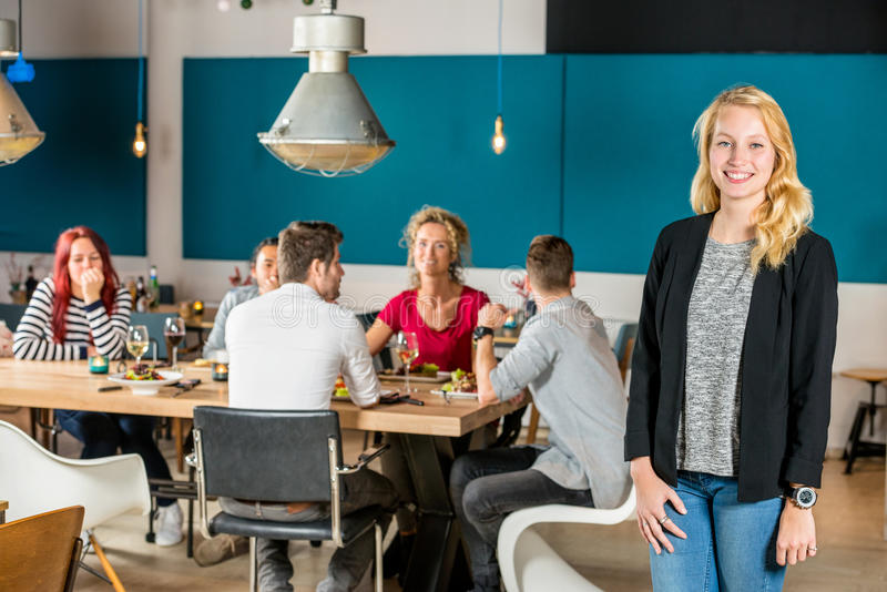 Portrait Of Happy Woman Standing At Restaurant. Portrait of happy women standing at restaurant with friends in background royalty free stock photography