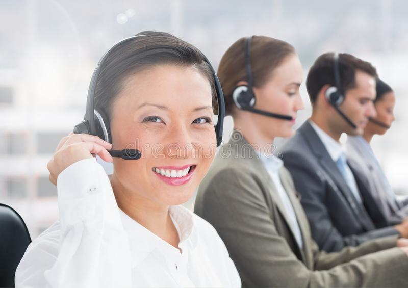 Portrait of happy woman talking on headset in call centre stock photos