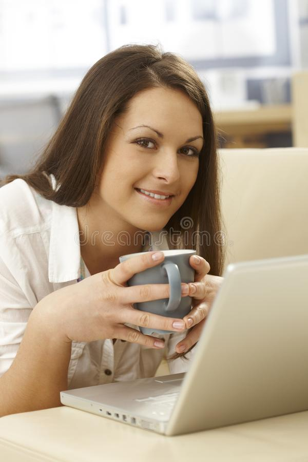 Portrait of happy woman with tea and laptop stock photo