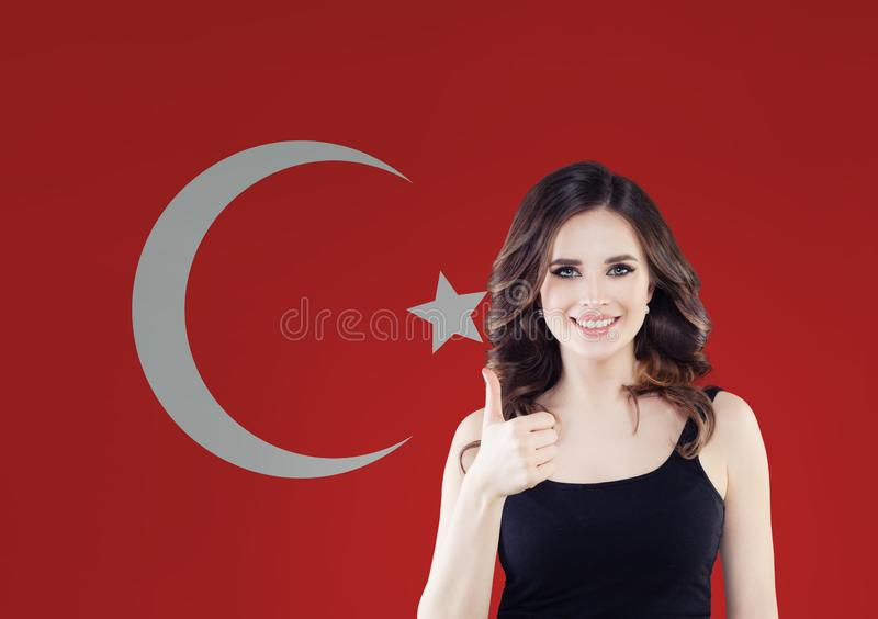 Portrait of happy woman with thumb up on Turkish flag background. Travel in Turkey royalty free stock photos