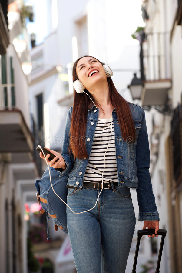 Happy woman walking with earphones and luggage outside royalty free stock images
