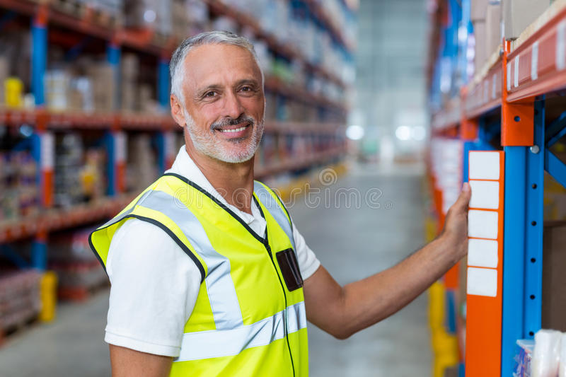 Portrait of happy worker is posing and looking the camera during work. In a warehouse royalty free stock image
