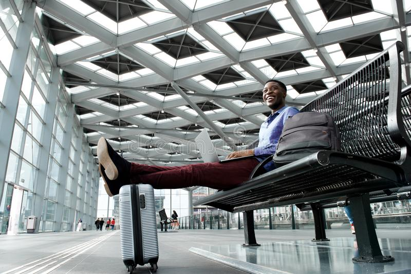 Happy young african american traveling businessman using laptop at station stock photos