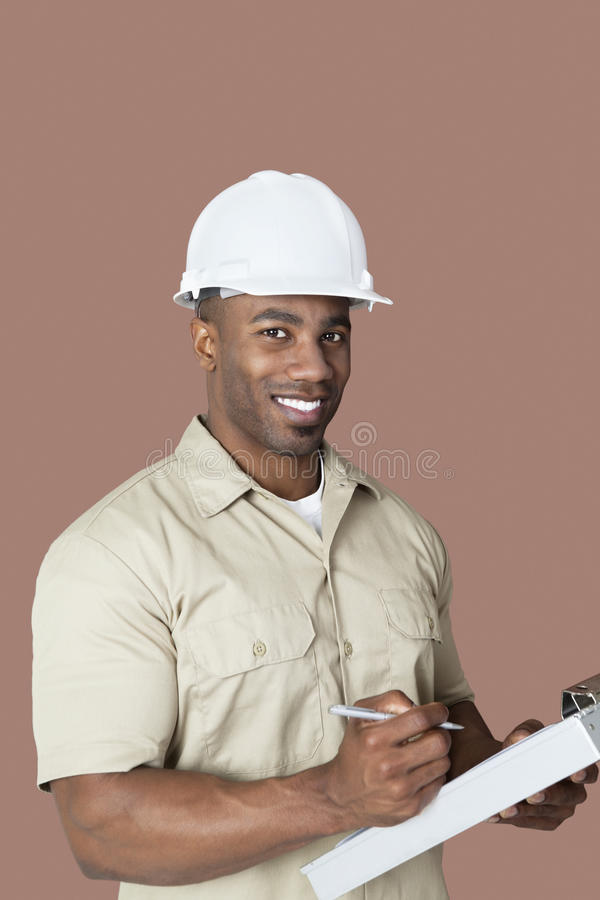 Portrait of happy young African male construction worker holding clipboard over brown background stock photos