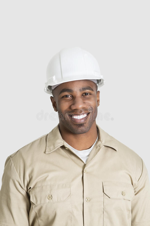 Portrait of happy young African male construction worker over gray background stock photography