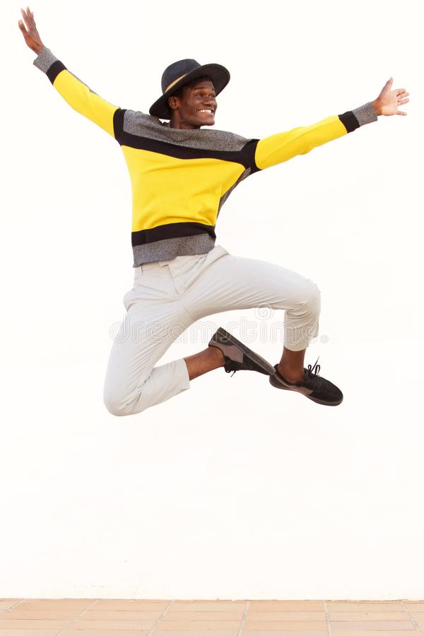 Happy young african man jumping in air over white background royalty free stock photo