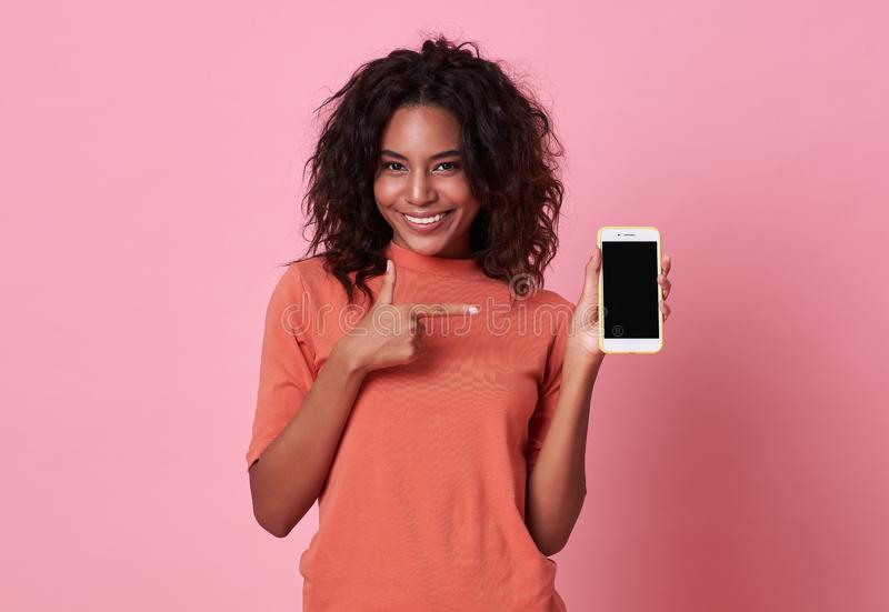 Portrait of a happy young african woman hand pointing at  blank screen mobile phone isolated over pink background royalty free stock images