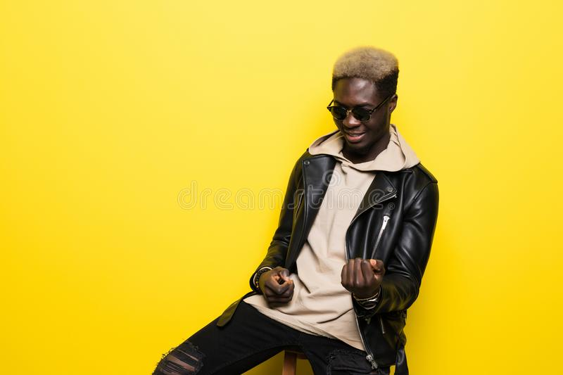 Portrait of a happy young afro american man listening to music with headphones and playing on invisible guitar over yello royalty free stock photos