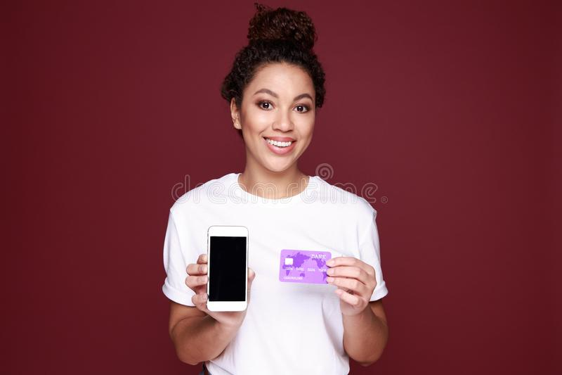 Portrait of an excited young african woman showing blank screen mobile phone isolated over pink stock photo