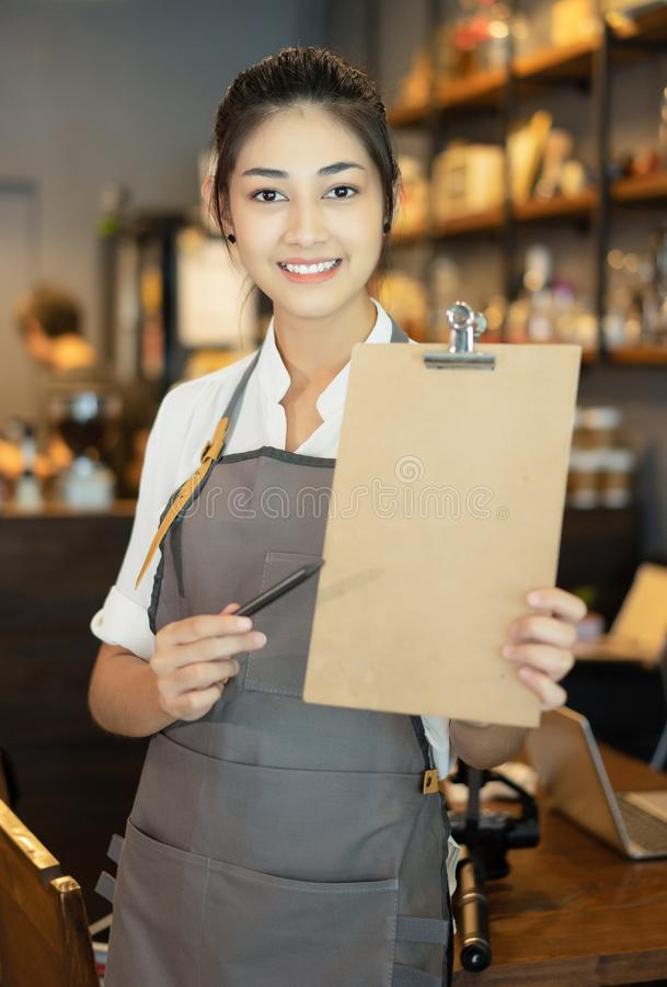 Portrait of a happy young Asian barista in apron smiling holding menu on clipboard and looking at camera on beside coffee machine royalty free stock photography