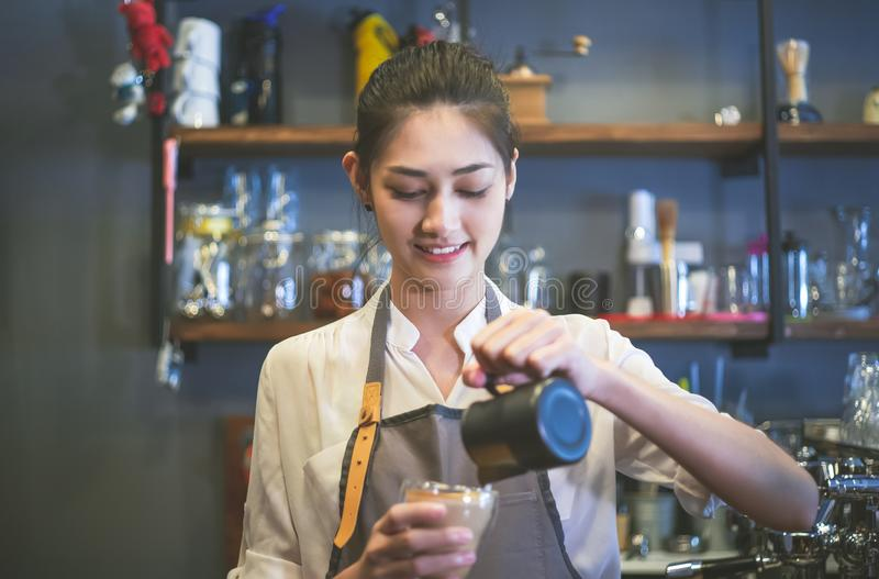 Portrait of a happy young Asian barista in apron smiling preparing and pouring milk into hot cup while standing at cafe. Startup royalty free stock image