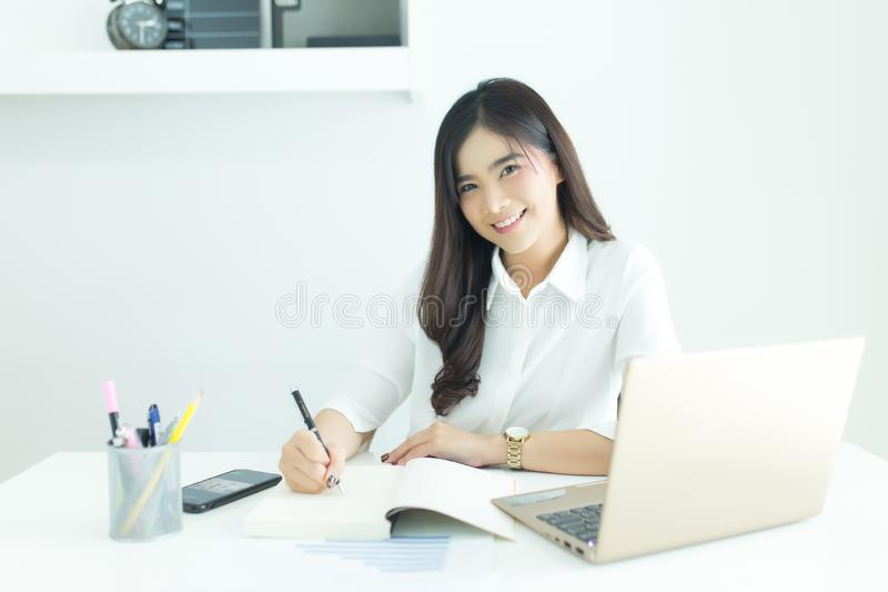 Portrait of happy young asian business woman looking at camera at her workplace. royalty free stock photos