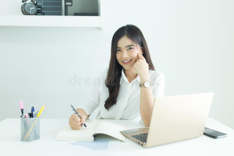 Portrait of happy young asian business woman looking at camera at her workplace. stock photo