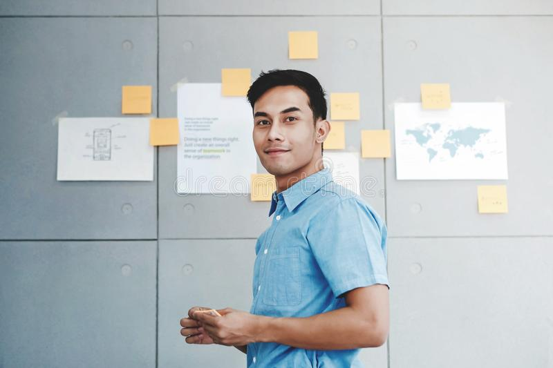 Portrait of Happy Young Asian Businessman in Office Meeting Room. Document`s Data Plans and Project as background stock photography