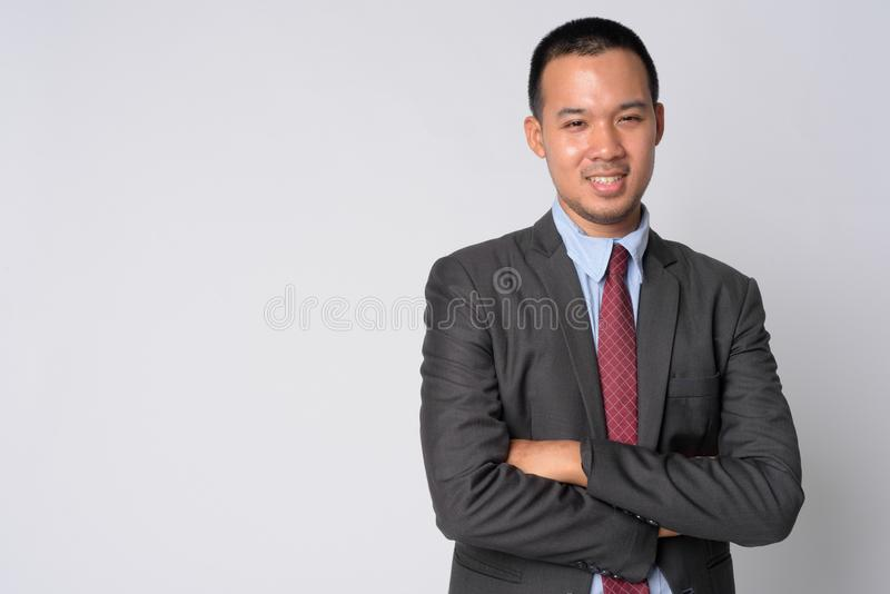 Portrait of happy young Asian businessman smiling with arms crossed stock photo