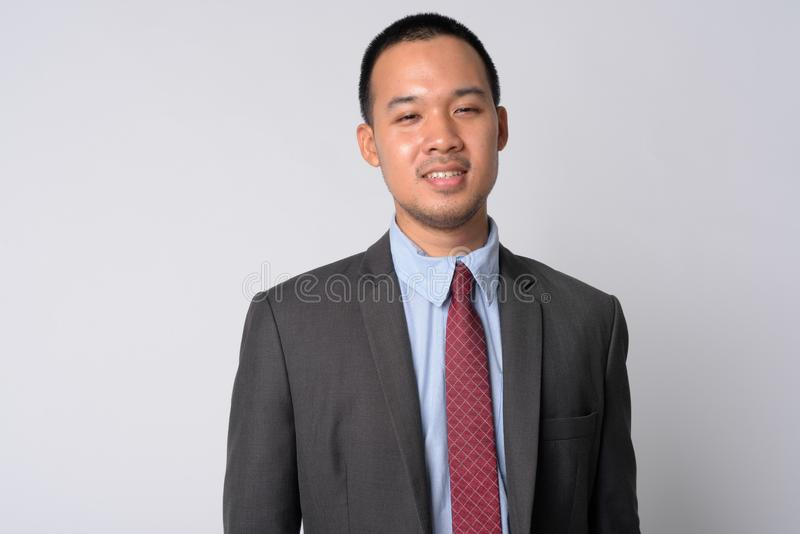 Portrait of happy young Asian businessman in suit smiling stock photography