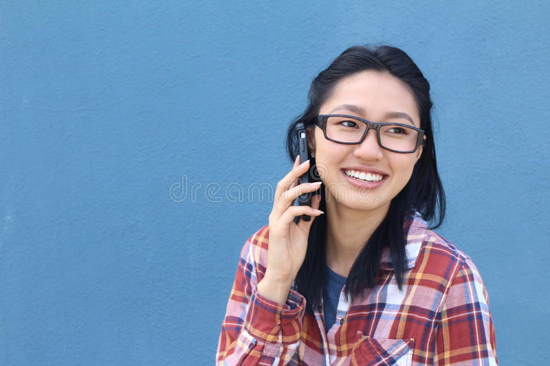 Portrait of happy young Asian woman talking on the phone with copy space stock images