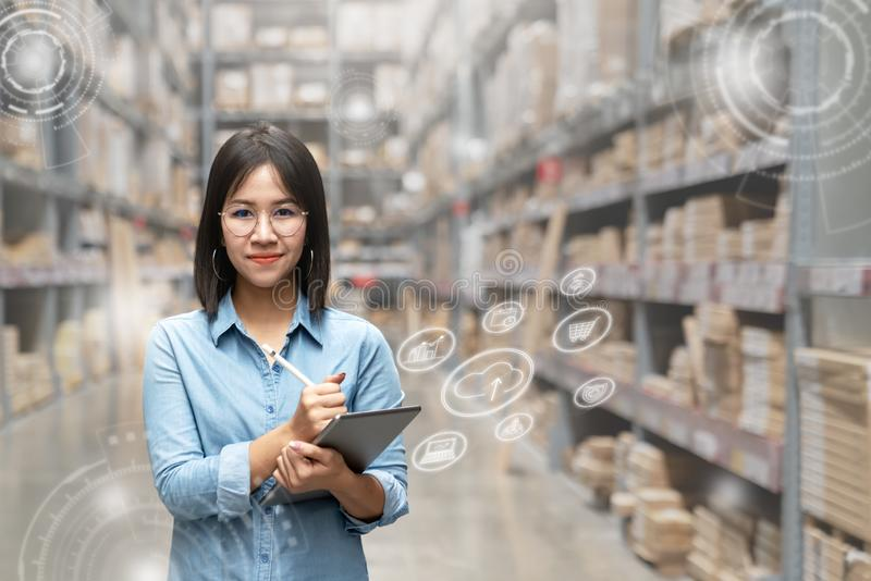 Portrait of happy young attractive asian entrepreneur woman looking at camera using smart tablet in warehouse with inventory royalty free stock photography