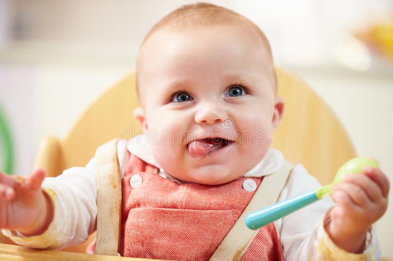 Portrait Of Happy Young Baby Boy In High Chair stock images