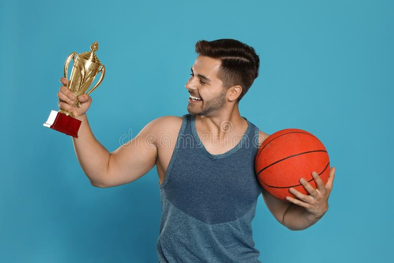 Portrait of happy young basketball player with gold trophy cup royalty free stock image