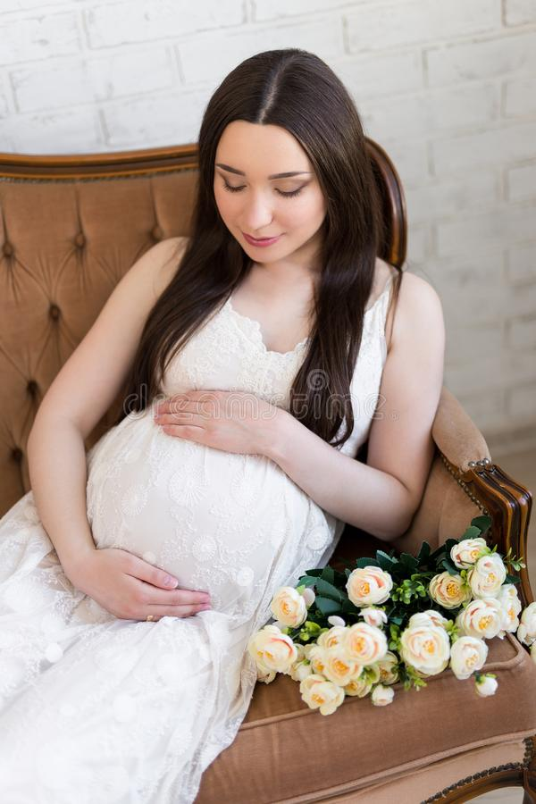 portrait of happy young beautiful pregnant woman sitting on vintage sofa with flowers royalty free stock photo