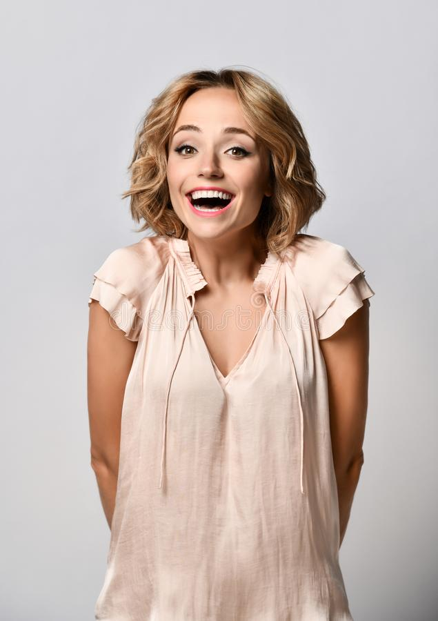 Portrait of a happy young blonde woman in a beige satin blouse celebrating success isolated on a light background. stock photo