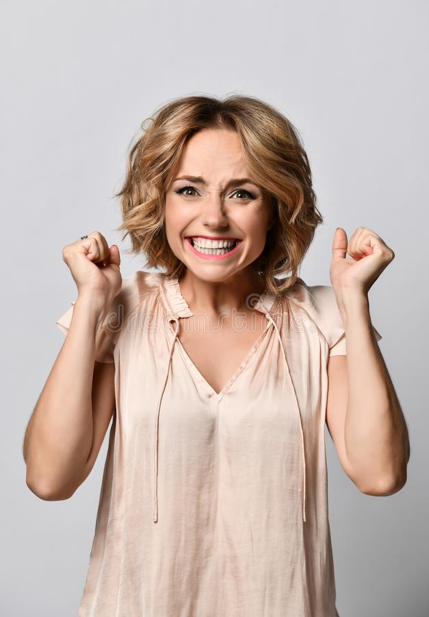 Portrait of a happy young blonde woman in a beige satin blouse celebrating success isolated on a light background. royalty free stock photos
