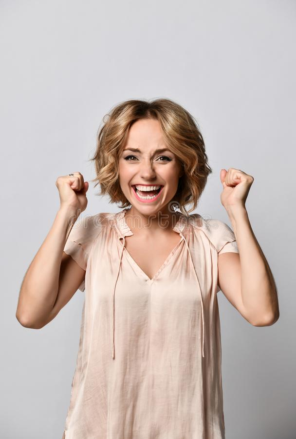 Portrait of a happy young blonde woman in a beige satin blouse celebrating success isolated on a light background. royalty free stock photography