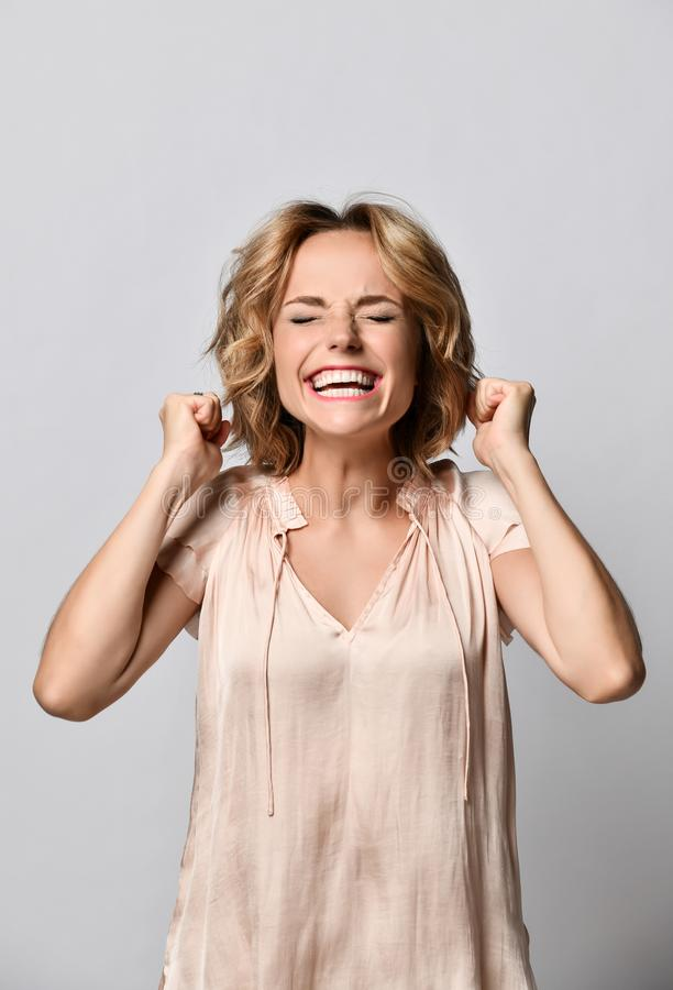 Portrait of a happy young blonde woman in a beige satin blouse celebrating success isolated on a light background. stock photos