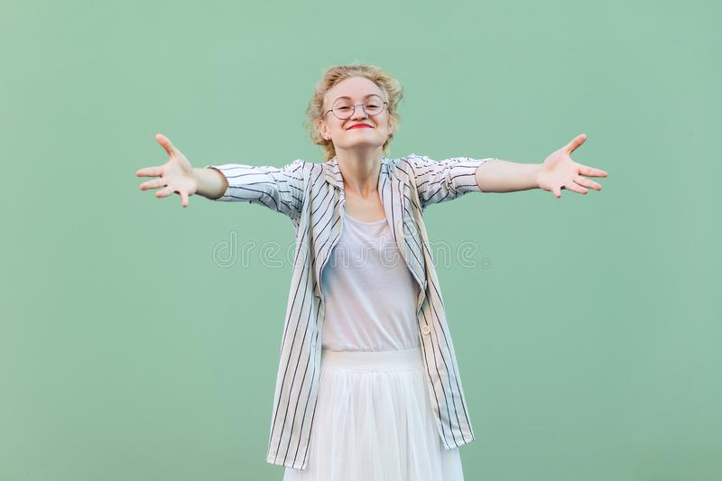 Portrait of happy young blonde woman in white shirt, skirt, and striped blouse with eyeglasses standing with raised arms, smiling stock photo