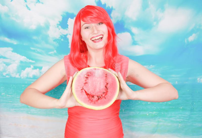 Portrait of happy young bright woman holding slice half of watermelon over colorful blue background stock photos