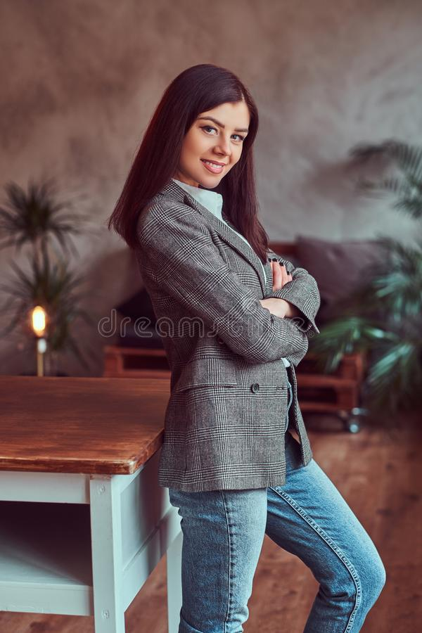 Happy young brunette woman dressed in a gray elegant jacket posing while leaning on a table in a room with loft interior royalty free stock image