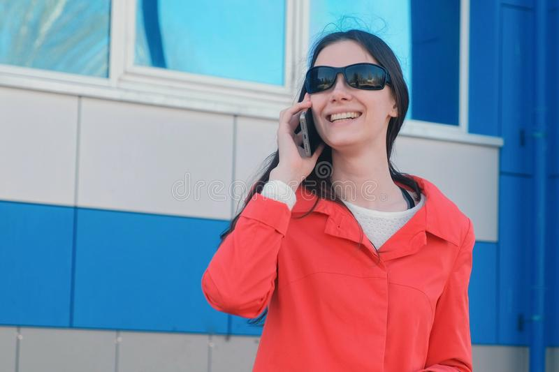 Portrait of happy young brunette woman in sunglasses speaks on the phone the beside blue building. stock image