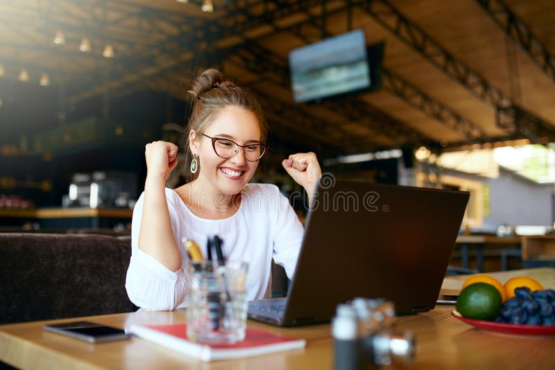 Portrait of happy young business woman celebrating success with arms up in front of laptop. Mixed race female won a lot stock photography