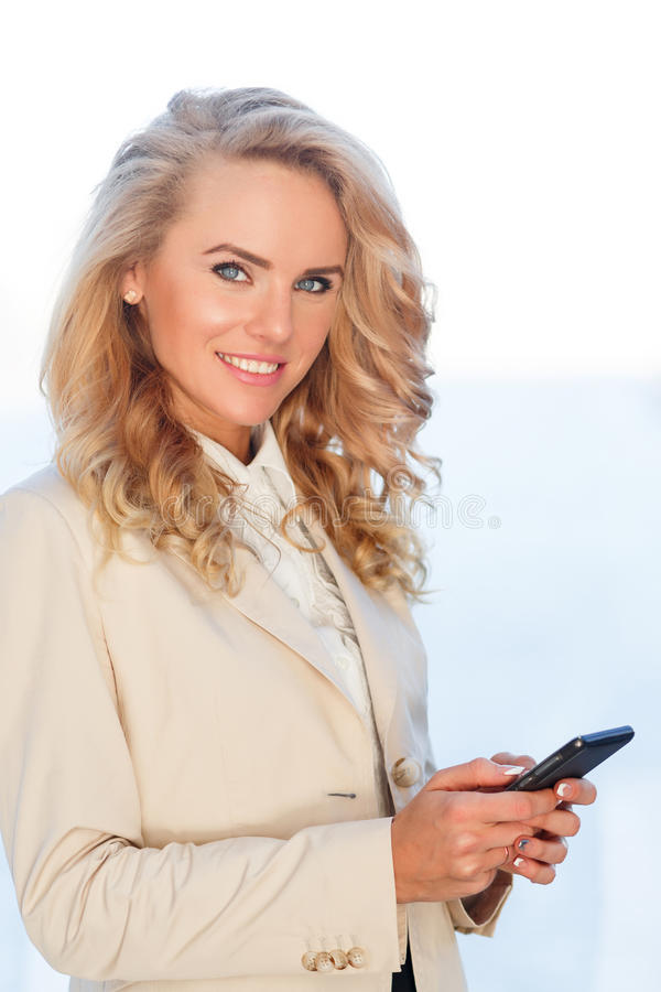 Portrait of happy young business woman checking her smartphone stock images