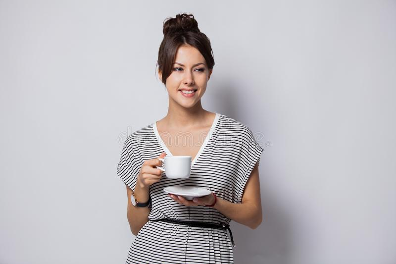 Portrait of a happy young business woman holding cup of coffee isolated over white background. stock photography