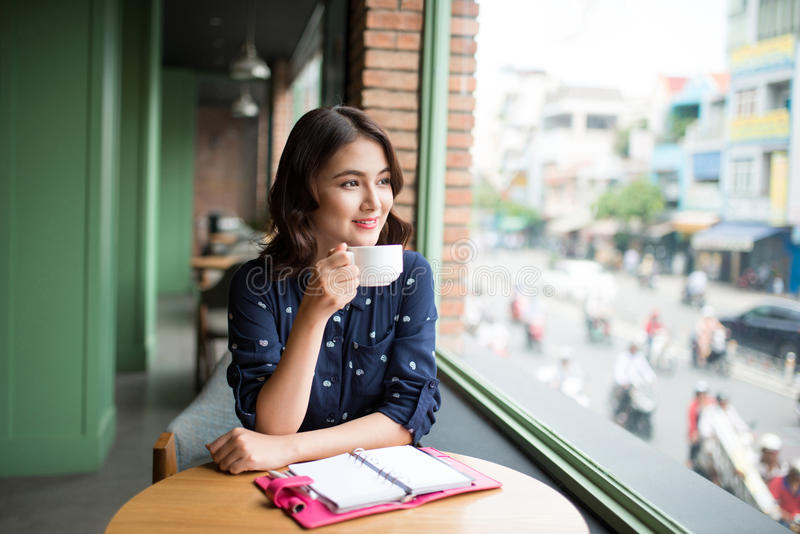 Portrait of happy young business woman with mug in hands drinking coffee in the morning at restaurant royalty free stock image