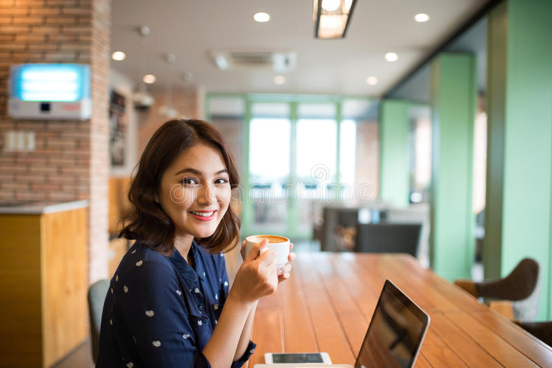 Portrait of happy young business woman with mug in hands drinking coffee in the morning at restaurant stock photos