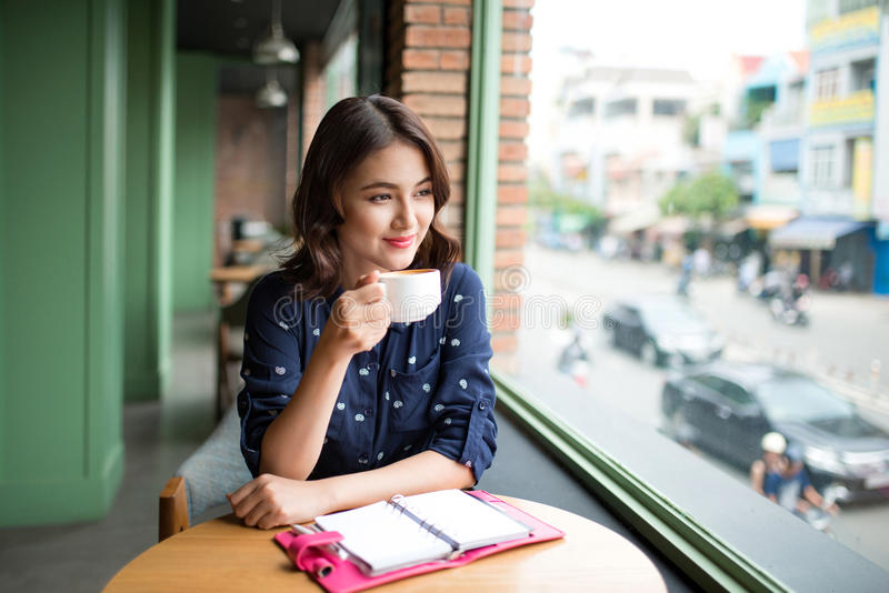 Portrait of happy young business woman with mug in hands drinking coffee in the morning at restaurant royalty free stock photos