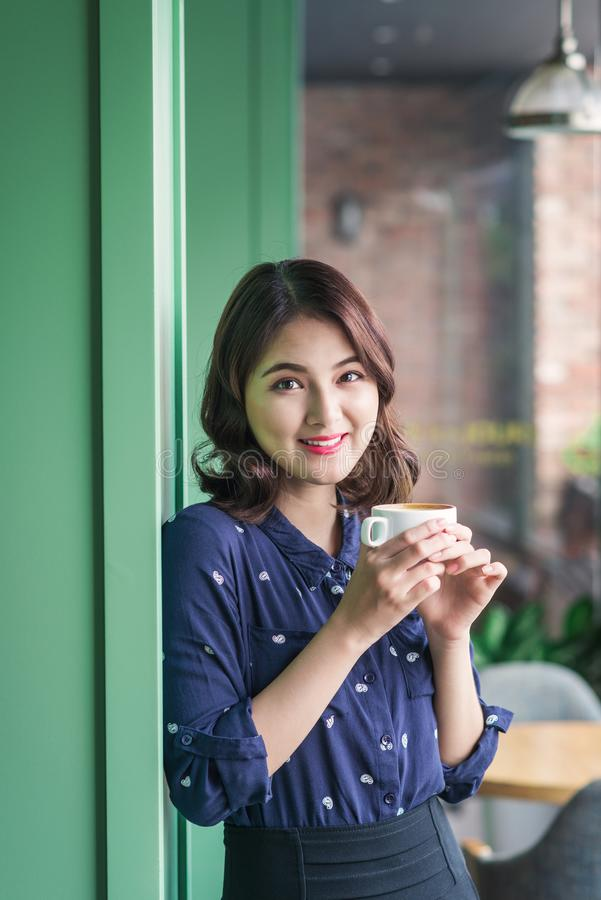 Portrait of happy young business woman with mug in hands drinking coffee in the morning at restaurant stock photography