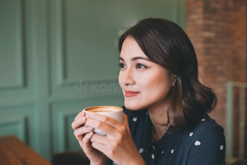 Portrait of happy young business woman with mug in hands drinking coffee in the morning at restaurant royalty free stock photo