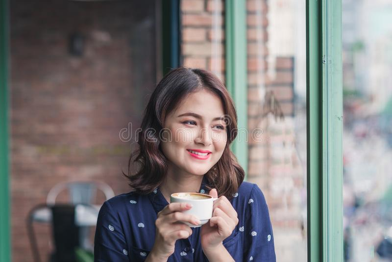 Portrait of happy young business woman with mug in hands drinking coffee in the morning at restaurant stock photo