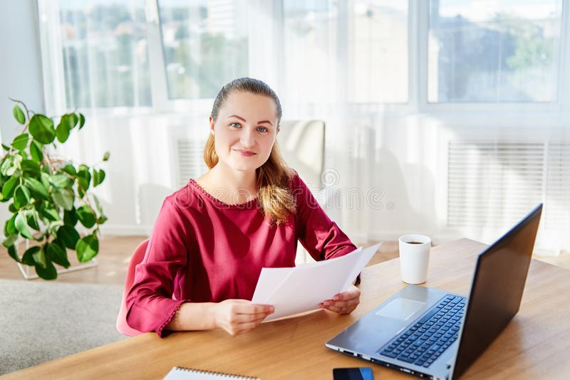 Portrait of happy young business woman sitting at wood desk with laptop and working with documents in modern office, copy space royalty free stock photography