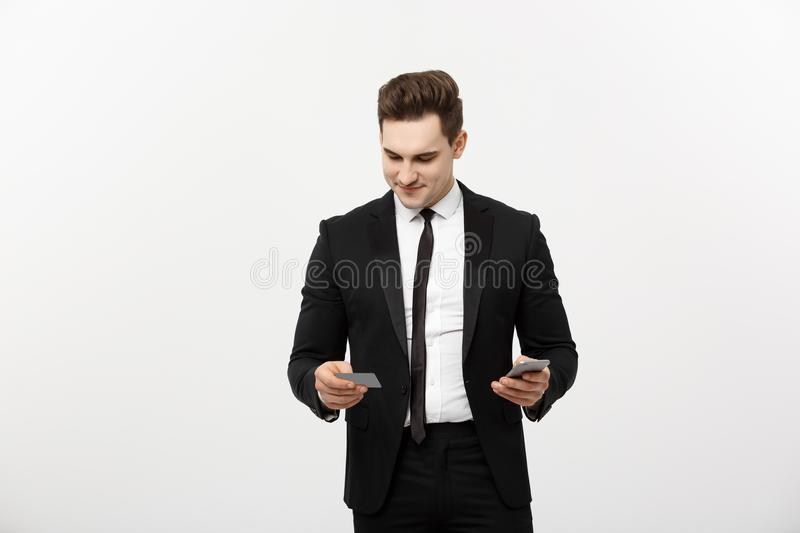 Portrait of happy young businessman in smart black suit standing over white wall background. Holding mobile stock photography