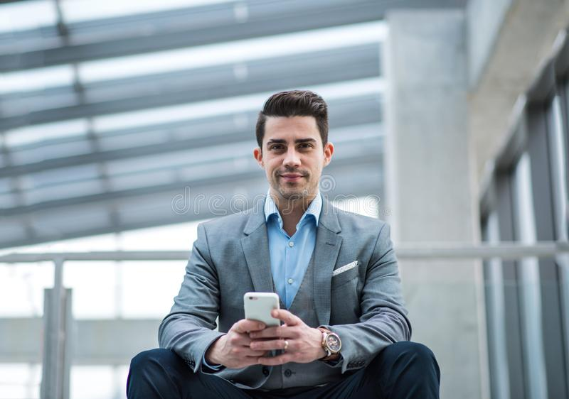 A portrait of young businessman with smartphone sitting in corridor outside office. royalty free stock photography