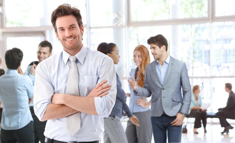 Portrait of happy young businessman. Standing in office lobby, people talking in background royalty free stock photo
